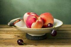Ainda vida com pêssegos e uvas Fotos de Stock Royalty Free