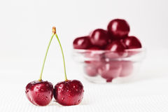 Ainda vida com pares de cereja vermelha e da bacia de vidro Imagens de Stock Royalty Free