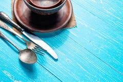 Ainda a vida com a placa cerâmica rústica marrom e a cutelaria velha ajustou-se na tabela de madeira azul Imagem de Stock Royalty Free