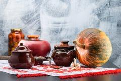 Ainda vida com potenciômetros, abóbora e alho do alimento em uma tabela tradi Fotografia de Stock Royalty Free
