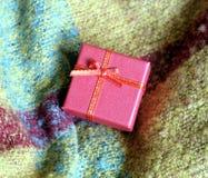 Ainda-vida com presente de época natalícia na caixa de cor vermelha pequena, coberta com a fita com curva, contra um fundo do pan imagens de stock