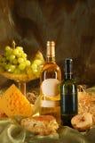 Ainda vida com queijo, pão, uvas e bott dois Imagem de Stock Royalty Free