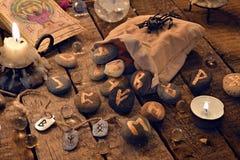 Ainda a vida com runas antigas e os cartões de tarô na vela iluminam-se Imagens de Stock Royalty Free