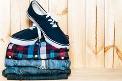Ainda vida com sapatilhas, a camisa e as calças de brim azuis no fundo de madeira, homem ocasional Fotografia de Stock