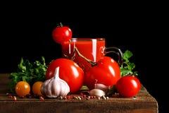 Ainda vida com suco dos tomates, da salsa, do alho e de tomate em placas de madeira Em um fundo preto Fotografia de Stock Royalty Free