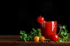 Ainda vida com suco dos tomates, da salsa, do alho e de tomate em placas de madeira Em um fundo preto Fotos de Stock Royalty Free
