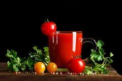 Ainda vida com suco dos tomates, da salsa, do alho e de tomate em placas de madeira Em um fundo preto Foto de Stock