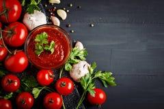 Ainda vida com tomates, alho, salsa, molho de tomate e pimenta em placas de madeira pretas Imagem de Stock