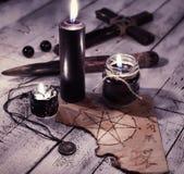 Ainda vida com três velas pretas, papel velho com pentagram e cruz Fotografia de Stock