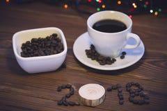 Ainda vida com um copo de café, uma bacia de doces e inscrição 2018 Imagem de Stock Royalty Free