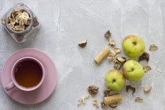 Ainda vida com um copo de chá cor-de-rosa, um frasco de vidro, umas flores secas e umas maçãs verdes Imagens de Stock