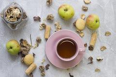 Ainda vida com um copo de chá, uns pires, um frasco de vidro, umas flores secas, umas maçãs e umas cookies Imagem de Stock Royalty Free