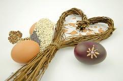 Ainda vida com um coração do salgueiro, dos ovos da páscoa e da silhueta do pássaro Imagem de Stock