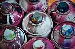 Ainda vida com um grande número latas de pulverizador coloridas usadas da pintura do aerossol que encontram-se na superfície de m Foto de Stock