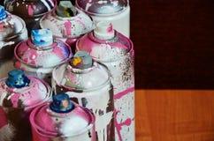 Ainda vida com um grande número latas de pulverizador coloridas usadas da pintura do aerossol que encontram-se na superfície de m Fotos de Stock Royalty Free