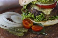 Ainda vida com um Hamburger na tabela de madeira Fotografia de Stock Royalty Free