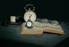 Ainda vida com um livro e os pulsos de disparo em cores escuras Foto de Stock Royalty Free