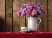Ainda vida com um ramalhete de flores do outono e de um retro um copo Imagens de Stock