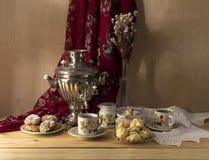 Ainda vida com um samovar, um chá, uns biscoitos e uns bolos em um close-up de madeira da tabela Fotografia de Stock