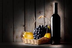 Ainda vida com um vinho da garrafa e uma cesta do fruto Imagens de Stock Royalty Free