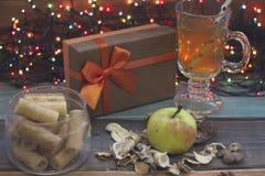 Ainda vida com uma caixa de presente, uma bacia de cookies, chá e uma maçã Fotos de Stock