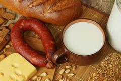 Ainda vida com uma caneca, um pão e uma salsicha do leite Imagem de Stock Royalty Free