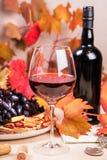 Ainda vida com uma garrafa e um vidro do vinho tinto, das uvas e do chocolate com morangos Imagem de Stock