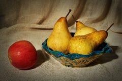 Ainda vida com uma maçã, as peras e um escorredor Imagens de Stock