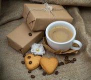 ainda vida com uma xícara de café com leite, uma cookie sob a forma de um coração, um presente no fundo Imagens de Stock