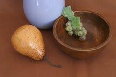 Ainda vida com uva da pera e a bandeja de madeira fotografia de stock royalty free