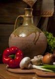 Ainda vida com vegetais contra um jarro Imagem de Stock Royalty Free