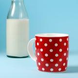 Ainda vida com vermelho, no às bolinhas, no copo do leite e na garrafa de vidro do vintage Imagens de Stock