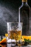 Ainda a vida com vidro e garrafa do conhaque, espirra das gotas em um fundo preto foto de stock