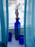Ainda a vida com vidros azuis e um vaso que está na soleira no inverno ajardinam Fotos de Stock