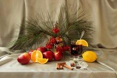 Ainda vida com vinho, a maçã, a laranja e as especiarias ferventados com especiarias Foto de Stock
