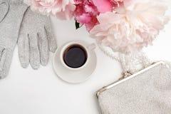 Ainda vida com xícara de café, flores das peônias e luvas na tabela clara Configuração lisa Vista superior Fotografia de Stock