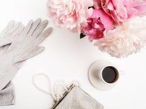 Ainda vida com xícara de café, flores das peônias e luvas na tabela clara Configuração lisa Vista superior Fotos de Stock Royalty Free