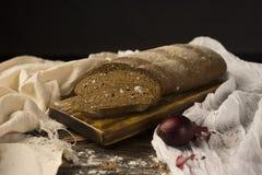 Ainda vida conceptual das partes de pão e de dois bulbos da cebola, sobre Imagens de Stock