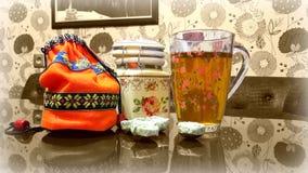 Ainda vida: copo de chá, açucareiro e um saco da fermentação na tabela na cozinha fotos de stock royalty free