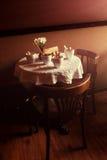 Ainda vida 1 Copos brancos da porcelana e um vaso do suporte de flores em uma tabela com uma toalha de mesa branca em um salão ma Fotografia de Stock Royalty Free