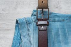 Ainda vida da calças de ganga com uma correia de couro marrom em um fundo de madeira claro Imagem de Stock Royalty Free