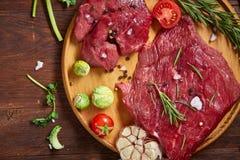 Ainda vida da carne crua da carne com os vegetais na placa de madeira sobre o fundo do vintage, vista superior, foco seletivo Imagem de Stock