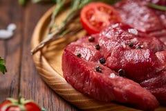 Ainda vida da carne crua da carne com os vegetais na placa de madeira sobre o fundo do vintage, vista superior, foco seletivo Fotografia de Stock