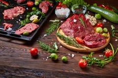 Ainda vida da carne crua da carne com os vegetais na placa de madeira sobre o fundo do vintage, vista superior, foco seletivo Imagens de Stock