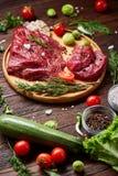 Ainda vida da carne crua da carne com os vegetais na placa de madeira sobre o fundo do vintage, vista superior, foco seletivo Foto de Stock