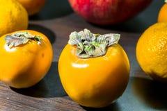 Ainda-vida da cozinha Frutos maduros integrais do caqui em uma tabela do marrom escuro Fotos de Stock Royalty Free