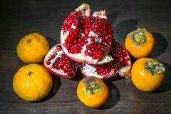 Ainda-vida da cozinha Frutos maduros integrais da romã, do mandarino e do caqui em uma tabela do marrom escuro Imagens de Stock Royalty Free