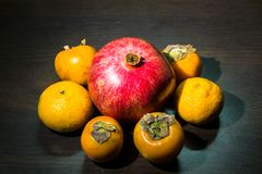 Ainda-vida da cozinha Frutos maduros integrais da romã, do mandarino e do caqui em uma tabela do marrom escuro Foto de Stock