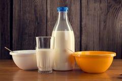 Ainda vida da garrafa do leite com vidro e as duas bacias plásticas sobre o fundo de madeira Fotografia de Stock