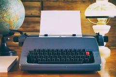 Ainda vida da máquina de escrever velha com folha vazia, globo e a lâmpada antiquado Imagem de Stock Royalty Free